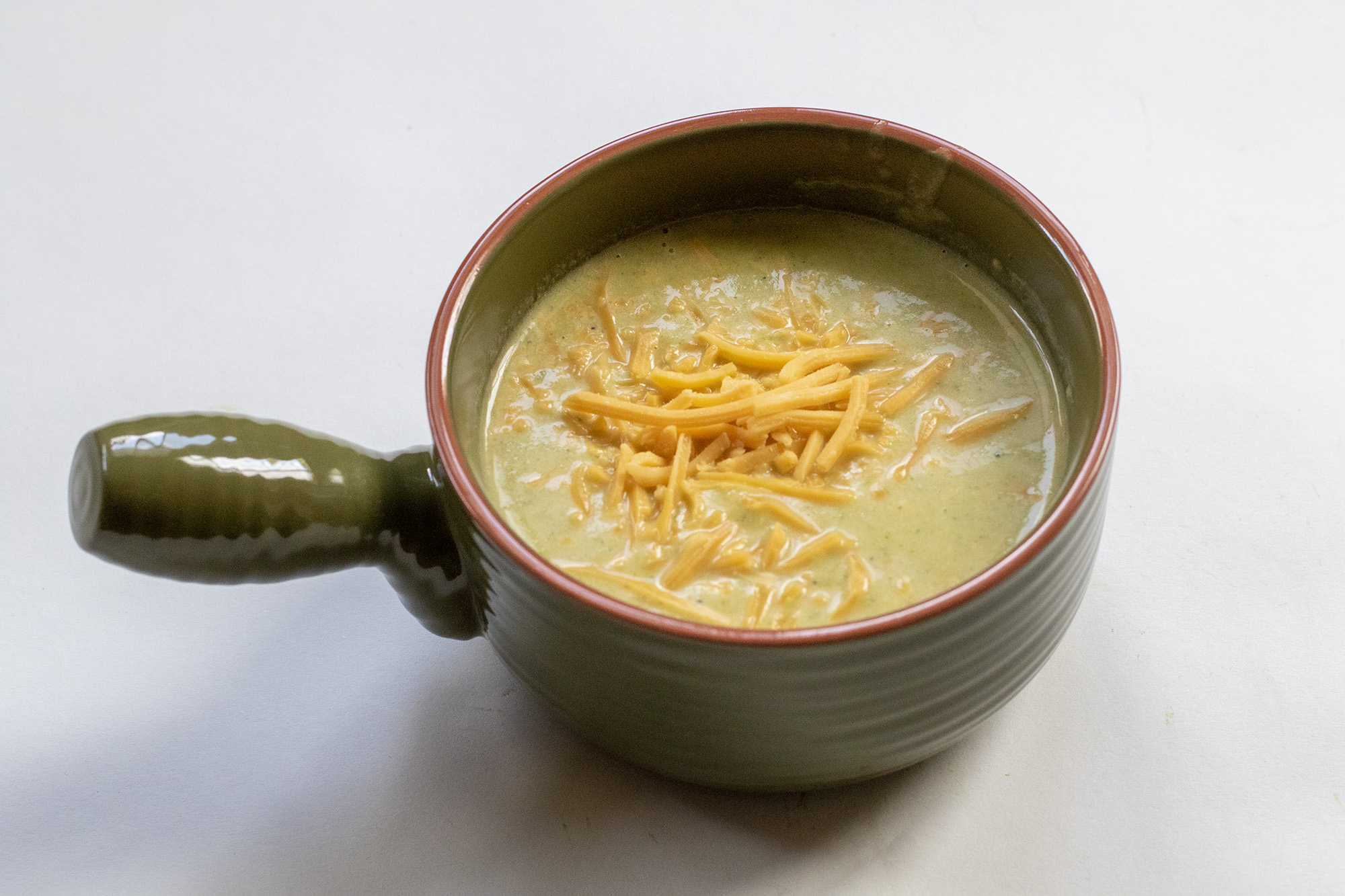 Broccoli Soup in a green bowl topped with shredded cheddar cheese laying on a flat white background.