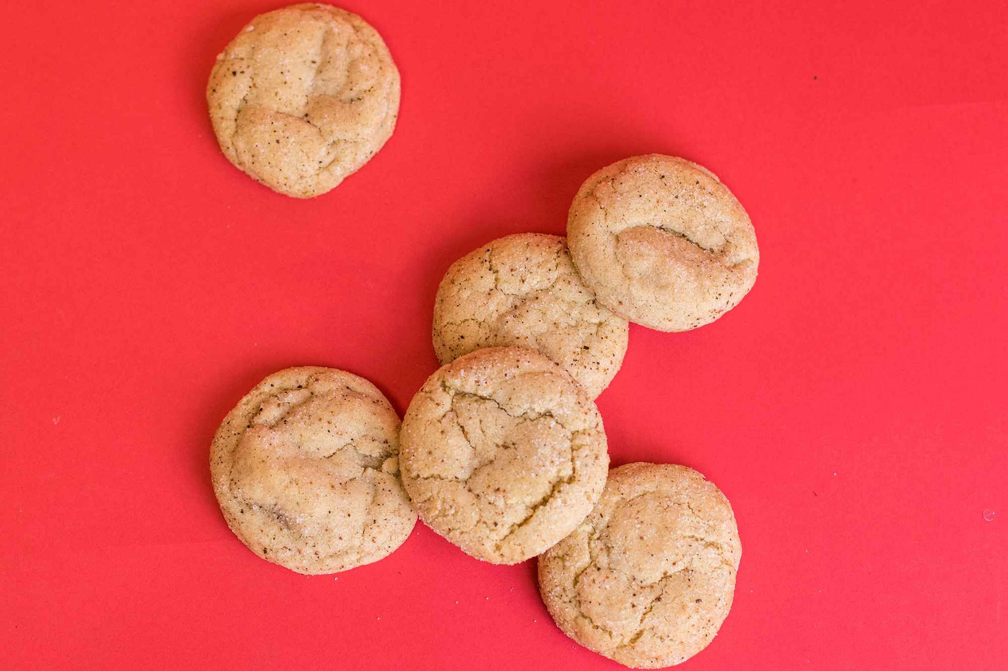 Egg Nog cookies spread out on a red background.